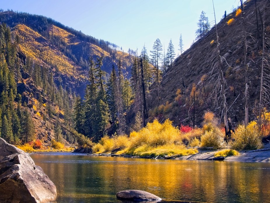 Fall colors reflected in the river flowing through the mountains in Washington.