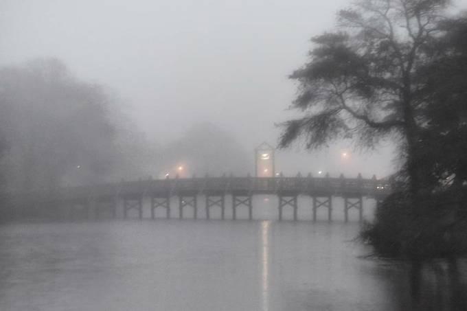 light shining in the fog across a foot bridge