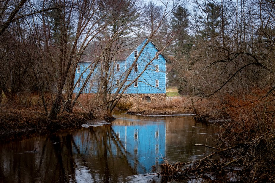 A winter view of the blue grist mill at historic Walnford.