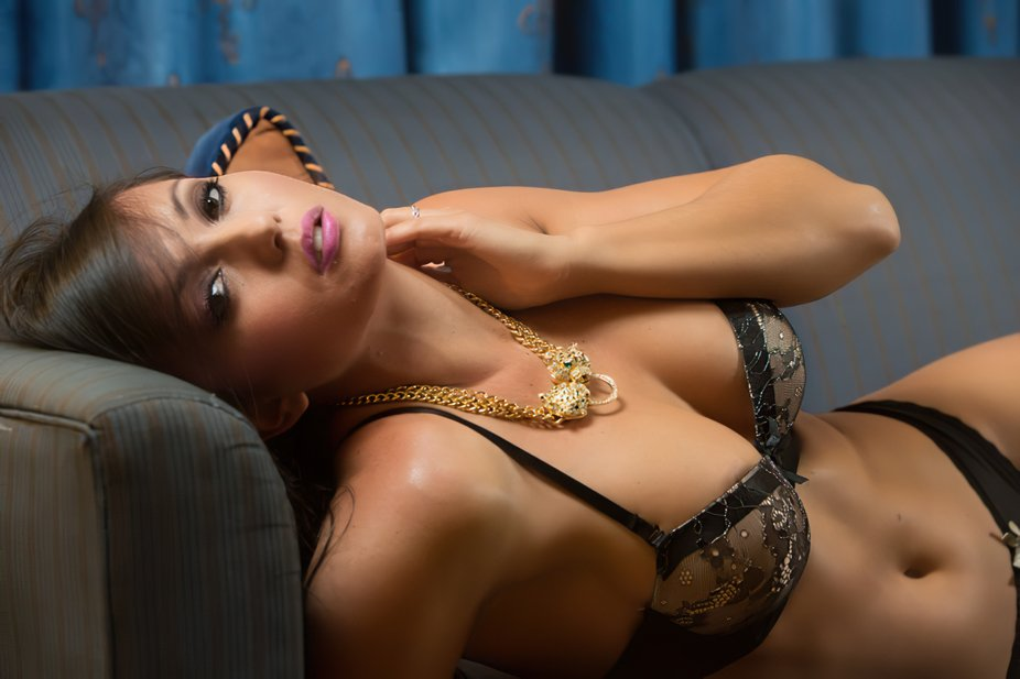 Beautiful Cora posing in lingerie on a couch.
