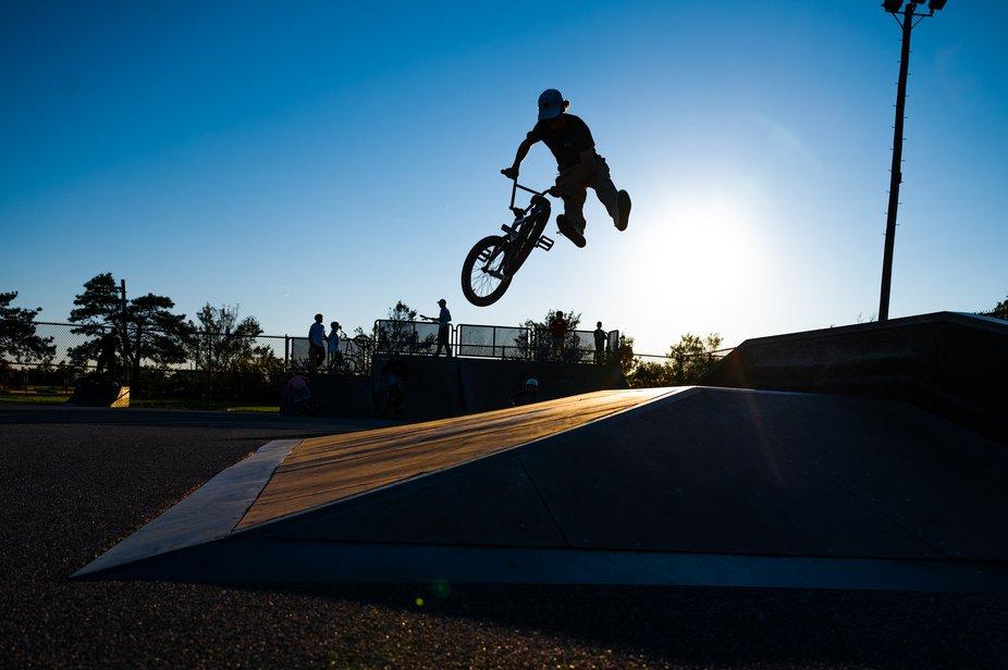 A boy catching air at a skate/bmx park on Long Island