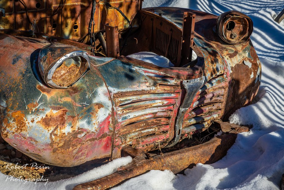 The sad old remains of a long gone car, sits in the snow on a winters day.