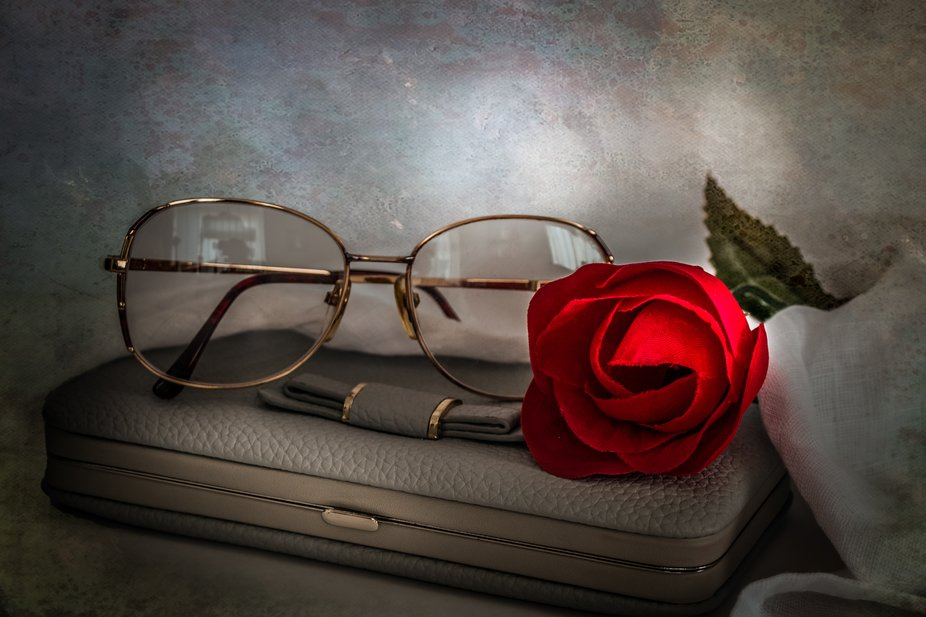 A still life image of reading glasses on purse accompanied by a rose.