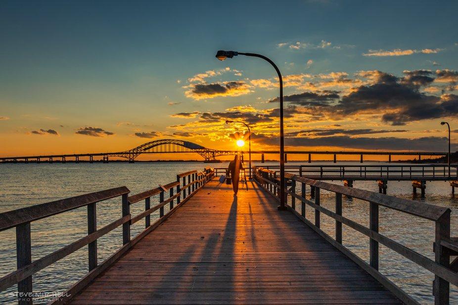 A fisherman walks towards the sun as it sets over the Fire Island Inlet Bridge, Captree, NY.