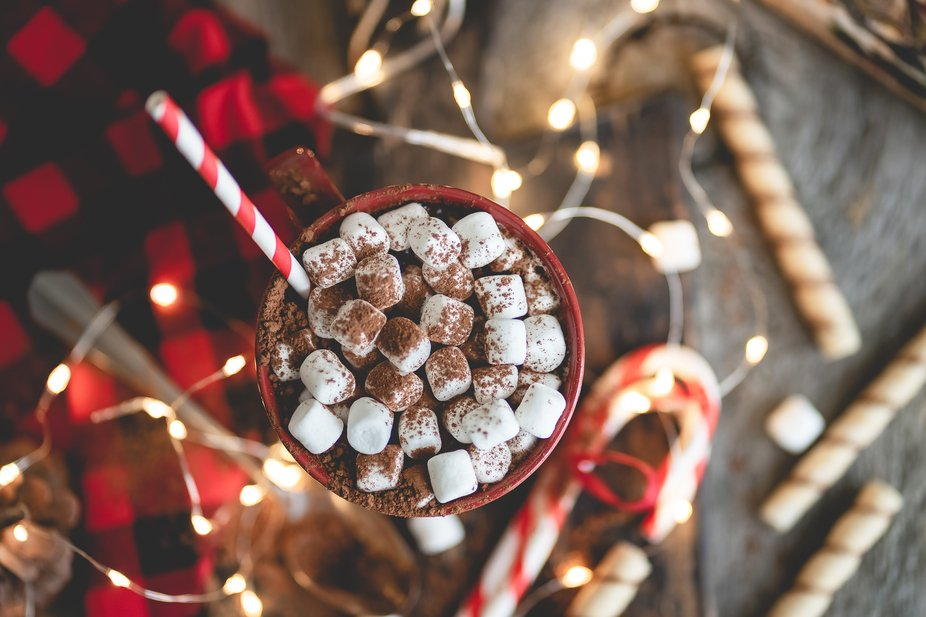 Top view of Hot chocolate with march-mellows in a red mug, covered with coco powder and surrounde...
