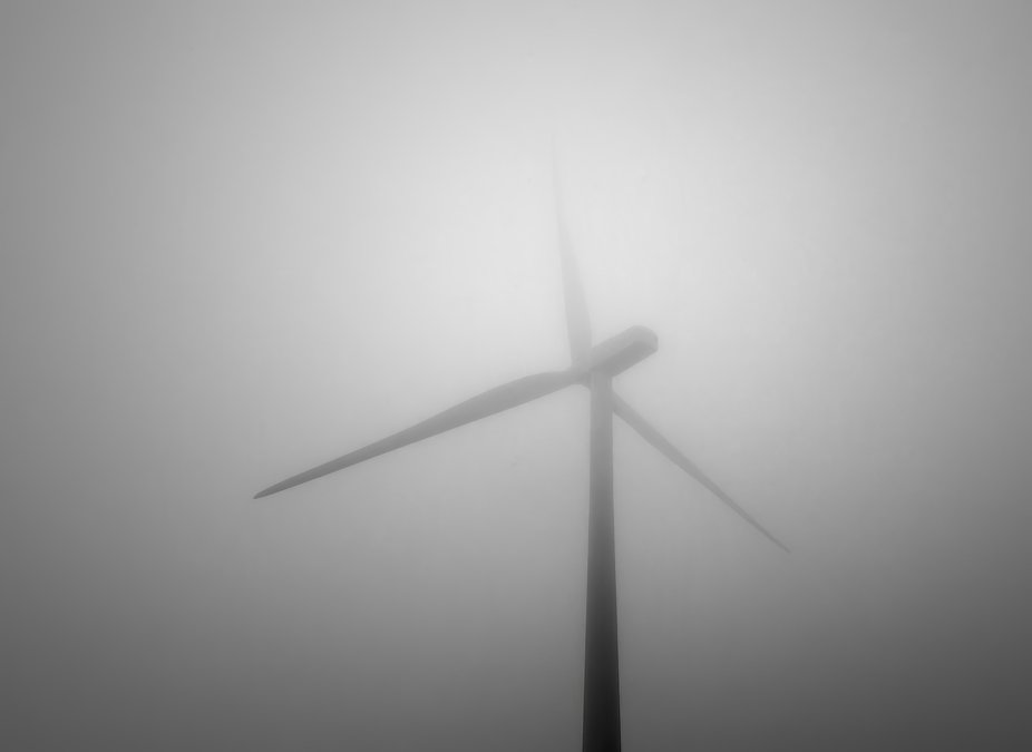 A wind turbine partially obscurred by fog