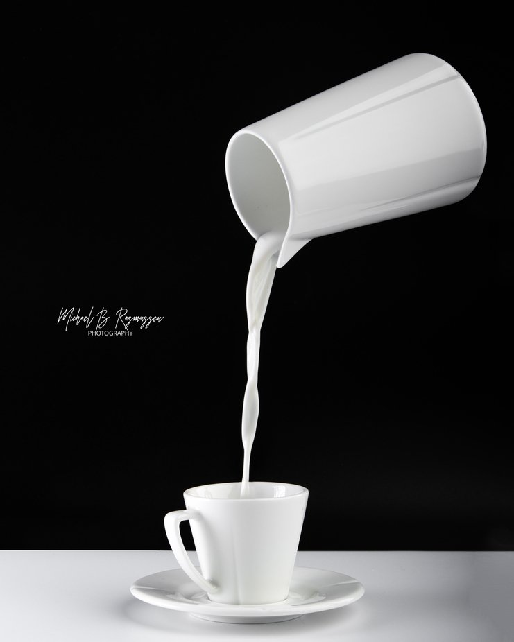 Studio image of milk being poured in a cup