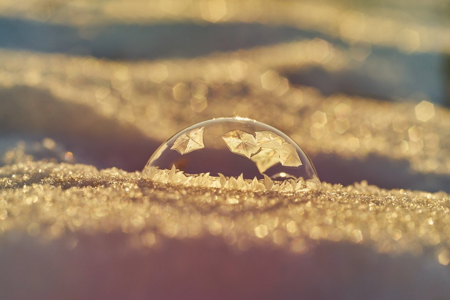 Frosty ornament on a half bubble on a snowy ground