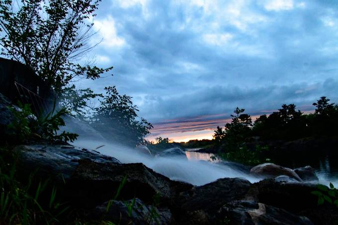 The beauty of a waterfall after a storm with clearing skies and sunset in the distance