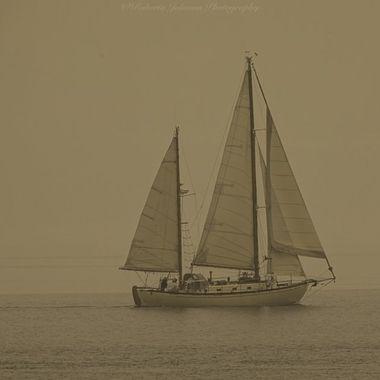 Sail boat with smoke filled skies. Hood Canal, Washington, USA