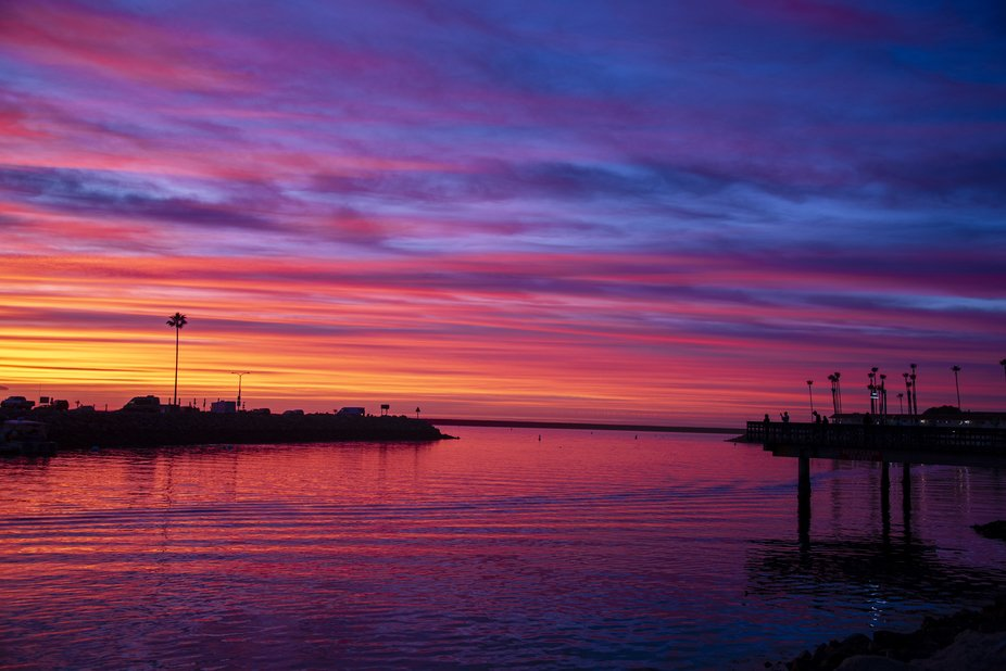 Oceanside, CA colorful sunset. Colorful sky and water at channel inlet.