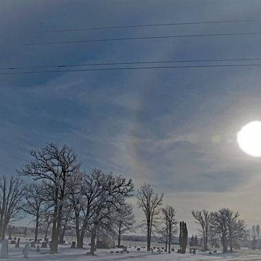Morning sundog over the hoarfrost covered trees of a cemetery