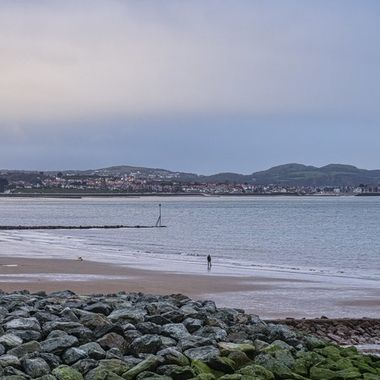 A lone walker on the beach at Old Colwyn