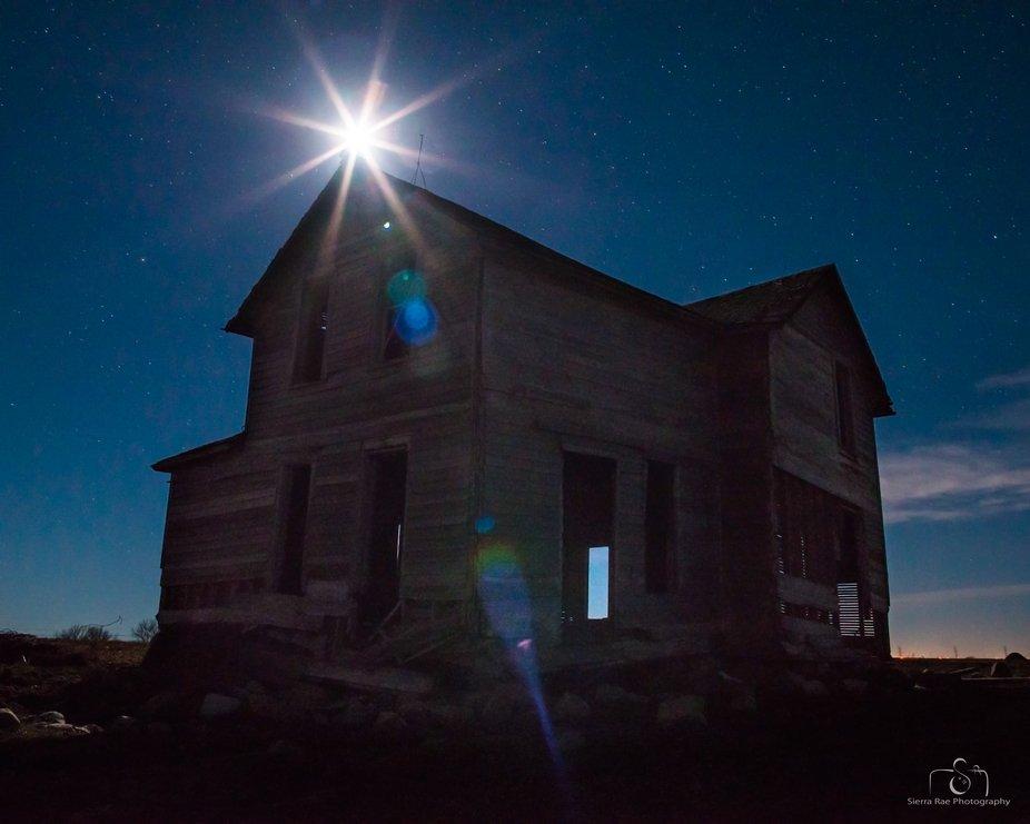 Abandoned farm near Epiphany, South Dakota. The moon flare site directly above the peak of the ro...