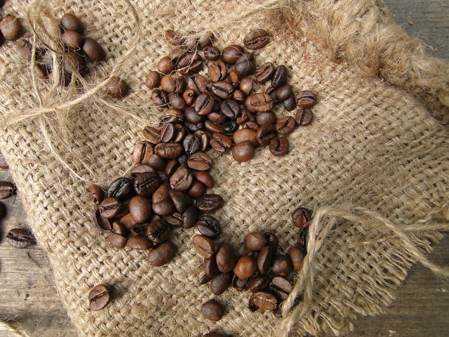 roasted brown coffee beans sprinkled on a burlap