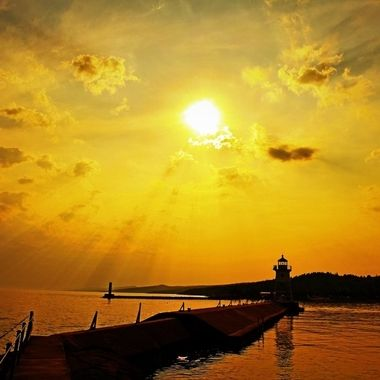 The sun breaking thru the clouds just in time for sunset over Grand Marais harbor