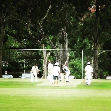 A friendly cricket match on the outskirts of the city