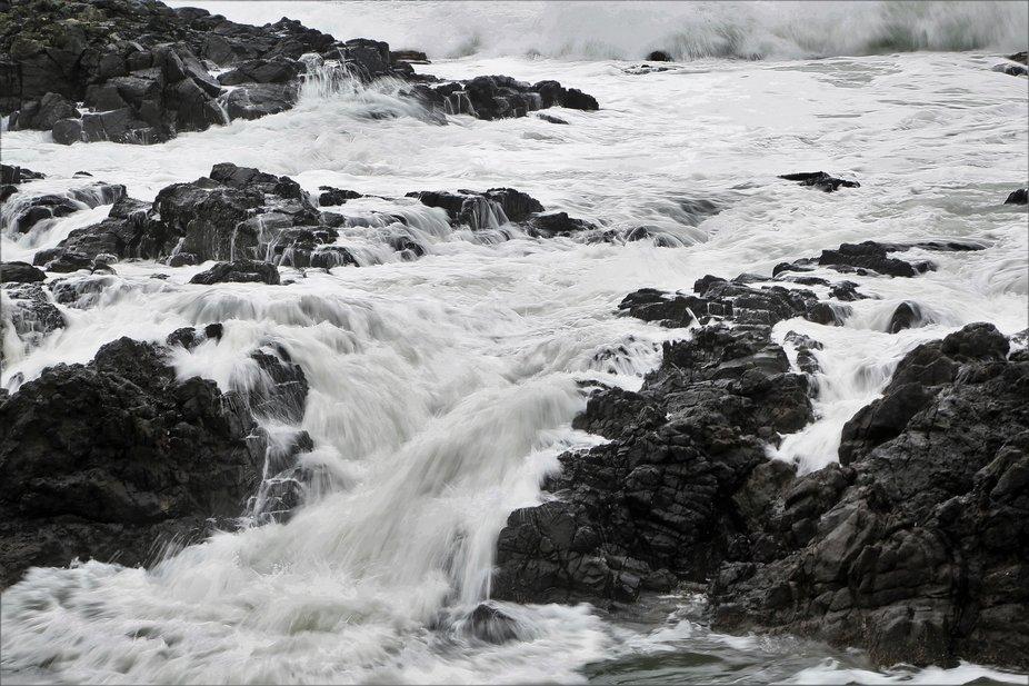 ocean waves cascade over basalt lava rocks on the Oregon coast