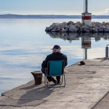 A former fisherman enjoys the view and the serenity of the sea from the land