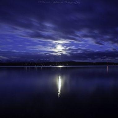 The snow moon setting from Hood Canal, Washington, USA