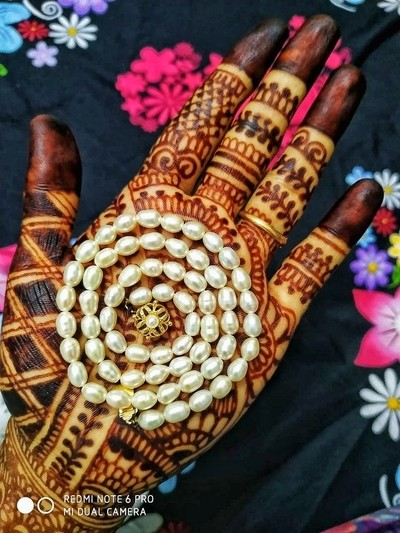 Happiness is looking at dark henna stained Women's hand that shows the esoteric creativeness of Indian women with loaded attractiveness.