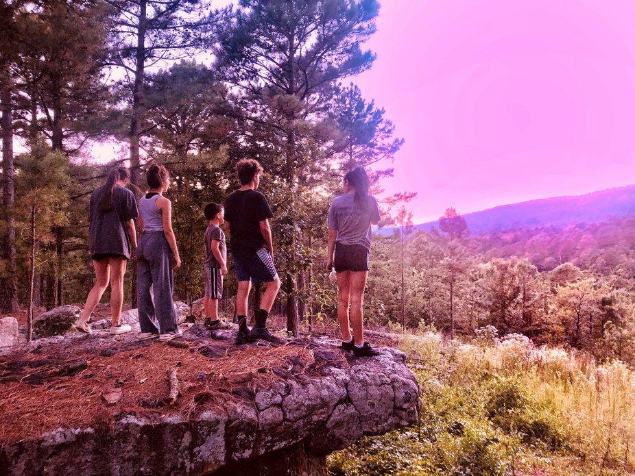 Kids watching beautiful pink sunset over mountain,