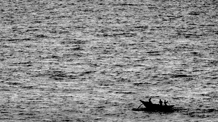 A silhouette of a traditional Sri Lankan fishing boat out at sea.