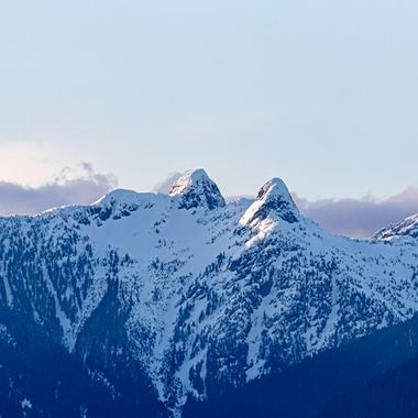 """The Lions (Squamish: """"Ch'ich'iyúy Elxwíkn"""" Twin Sisters) are a pair of pointed peaks (West Lion – 1,646 m (5,400 ft); East Lion – 1,606 m (5,269 ft)) along the North Shore Mountains in Metro Vancouver, British Columbia,  Canada. The city's BC Lions CFL football team is also named in their honour."""