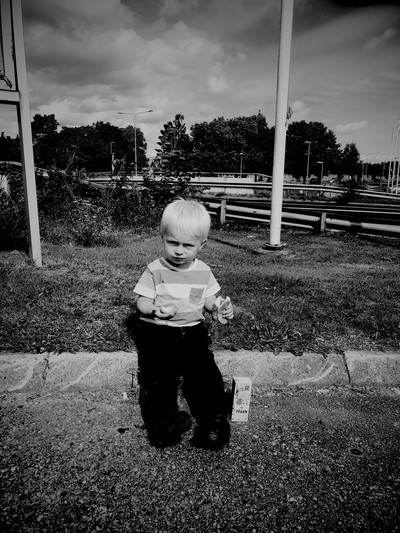 the boy takes a break and eats a sausage