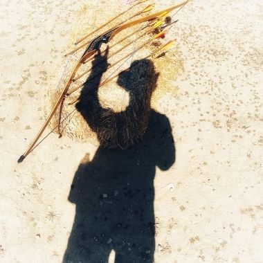 Standing person pointing at a bow and arrows on the ground!