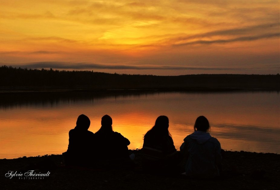 Four friends eating fast food, laughting, and enjoying a sunset on March 24th, 2021. They were ki...