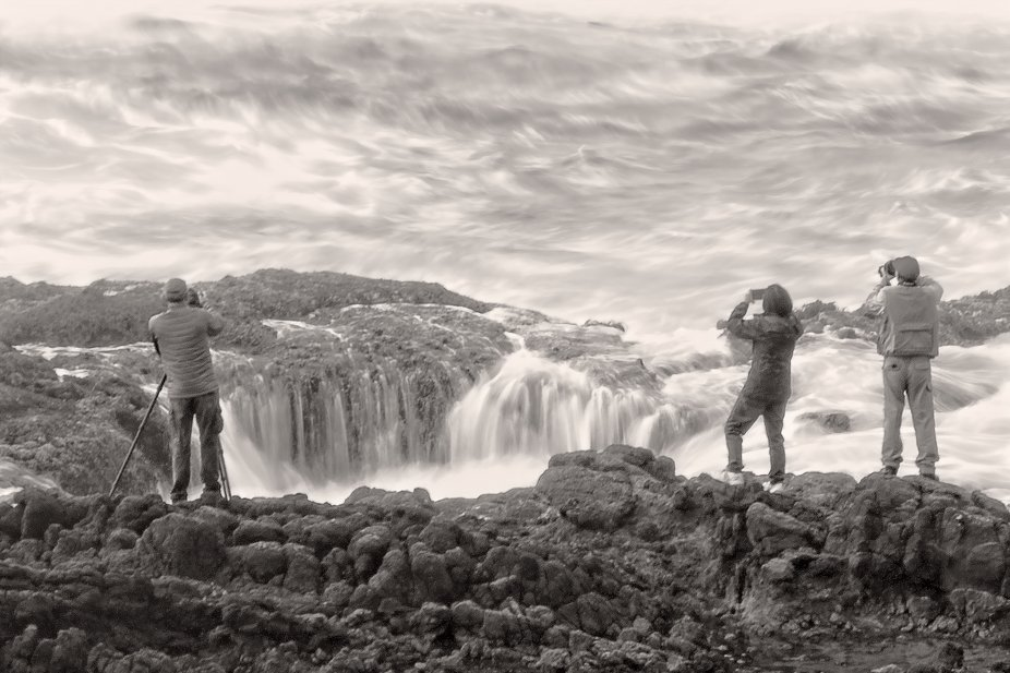 Photographers stand on the edge of Thor's Well on the Oregon coast.