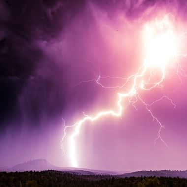 A summer monsoon in Sedona Arizona brings large lightning strikes across the sky. If you zoom in, you can see a small bat illuminated by the flash as it soars high