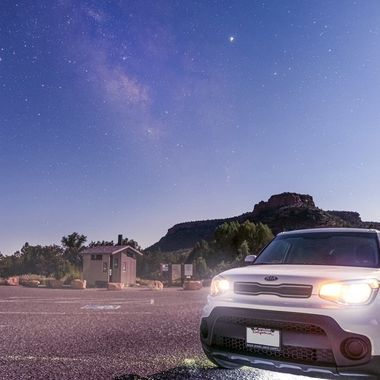 A summer milky way rises over the Sedona mountains with a white 2019 Kia Soul in the foreground