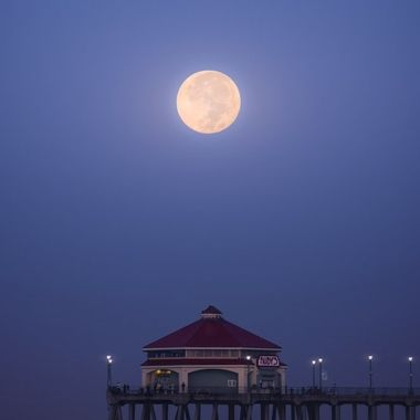 The harvest moon sets over the Huntington Beach pier in Southern California