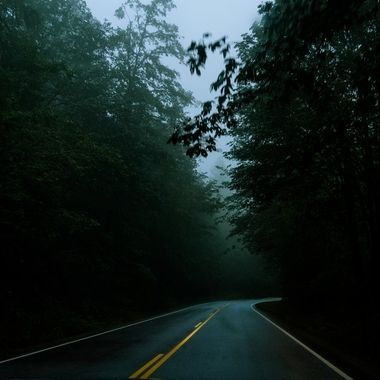 A dark and creepy scene of a highway cuts through an eerie and foggy mountain right after dusk