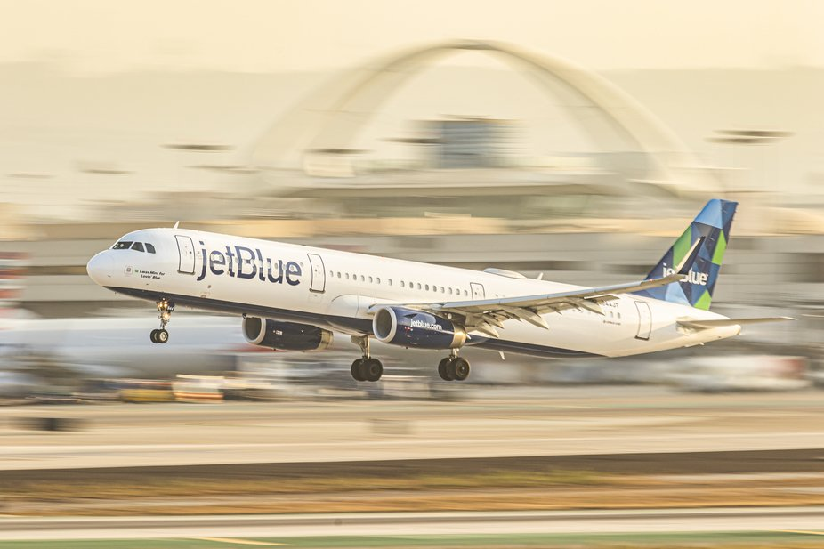 A panning shot of a jetBlue Airbus A321 departs Los Angeles International Airport