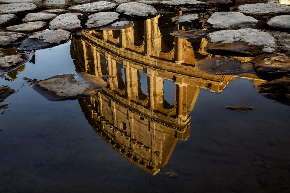 The Colosseum in Rome, Italy, reflected in a puddle of water after heavy rain