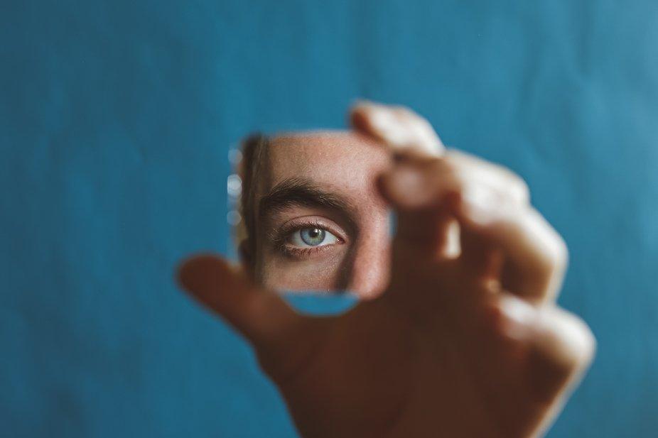 Close-up eye looking into broken mirror.