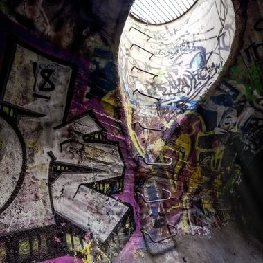 Graffiti covered walls of a concrete sewer see the light of day spill in