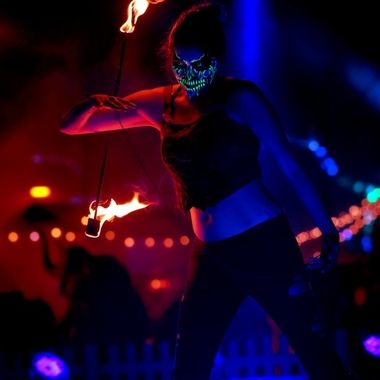 A female fire dancer performs with blacklight reactive makeup