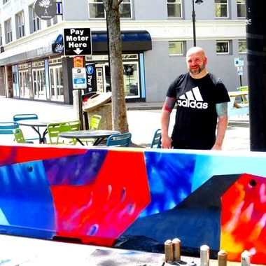 """I met James Chase today. I asked him what he was painting he said """"geometric shapes"""". He is a visual artist. He told me he is an art teacher at the Art Institute here in downtown Manchester New Hampshire.   www.neverfading.com  He and another artist are painting the large concrete roadblocks that are surrounding our downtown main street outdoor dining areas. Certainly making it look very pretty too! He told me he has already painted 40 of them in Nashua New Hampshire.   I do plan to go back very soon and do a photoshoot exclusively of the downtown roadblock art. It was just way too dangerous with all of the traffic going by when I was there this morning. The artwork is done on the inside and the outside of each roadblock. I checked it all out and know where I want to shoot. I am excited to return soon. Downtown Manchester New Hampshire 4/24/21"""