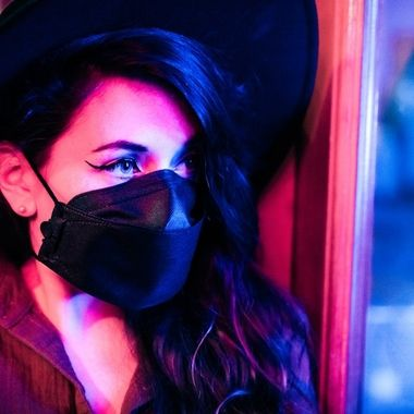 A masked model poses in an outdoor dining and shopping part of Old Town Orange. Photography by Chris Cornish. Wardrobe by Josie Austin. Model is Kaelyn Brandt
