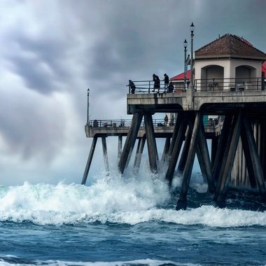 A dark and cloudy day over the Huntington Beach Pier in Southern California. Large waves crash against the supports while people fish from above