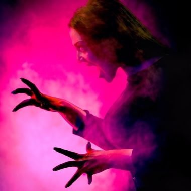 Portrait of a female vampire with long black hair and dark evil hands. Halloween and Horror inspired. The model was shot against a black background with theatrical lighting and special effects