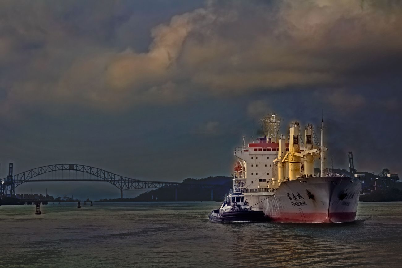 Early morning view of a tugboat pushing a Chinese cargo ship to the shoreline, to await funds (cash) that will be used to pay entry into the locks on the Pacific end of the Panama Canal.
