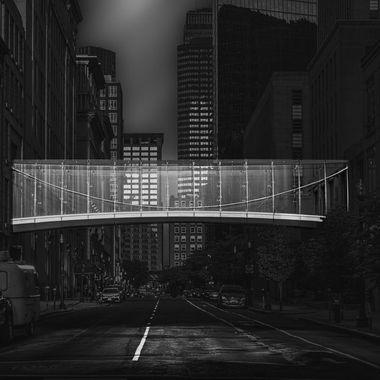 Glass bridge over street in city