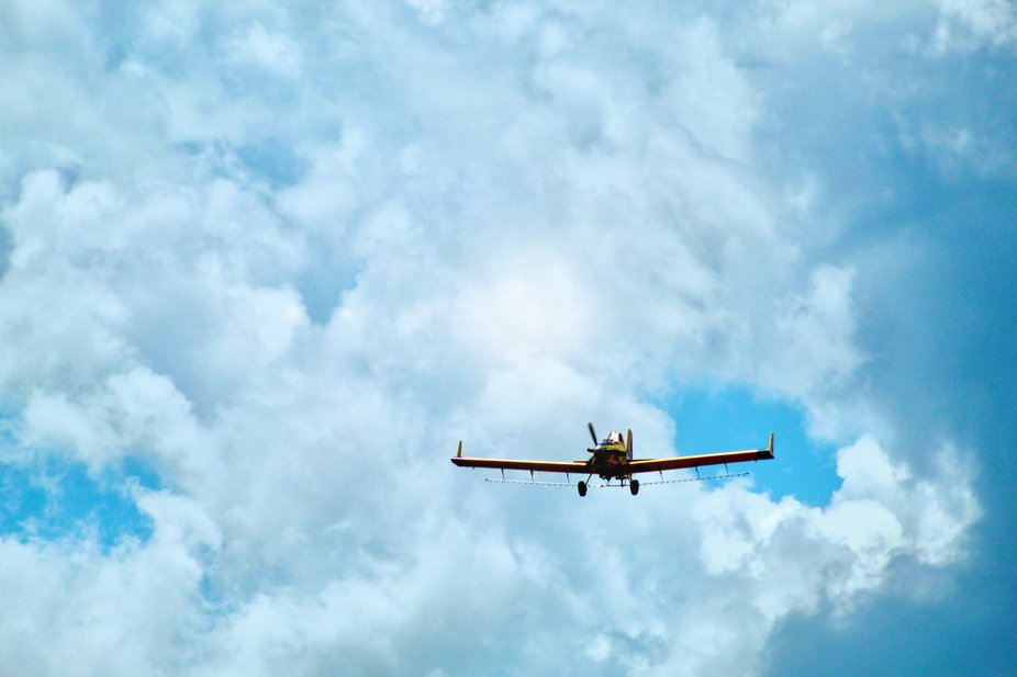 A crop duster spraying a field in Spring in Southeast Oklahoma