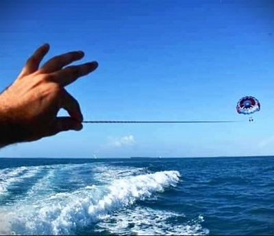 """Pic captured of """"illusion"""" of hand holding string from which a parachute is attached."""
