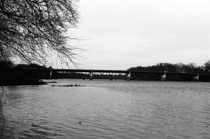 The effects of modernization requires that the new replace the old, an old railroad bridge stands in a state of dysrepair while the new modern bridge stands ever present.